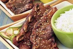 Two slabs of Korean beef barbecue ribs next to a bowl of white rice.