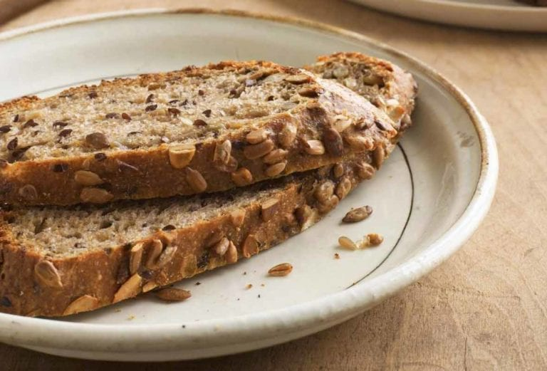 Two slices of no-knead pumpkin-sunflower seed bread on a plate, behind the rest of the loaf