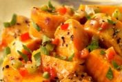 A plate of sweet potato salad sprinkled with cracked pepper, chopped parsley, and pickled pepper relish