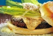 A Caesar salad burger--hamburger on a bun with melted cheese, Parmesan cheese, romaine lettuce and Caesar mayonnaise