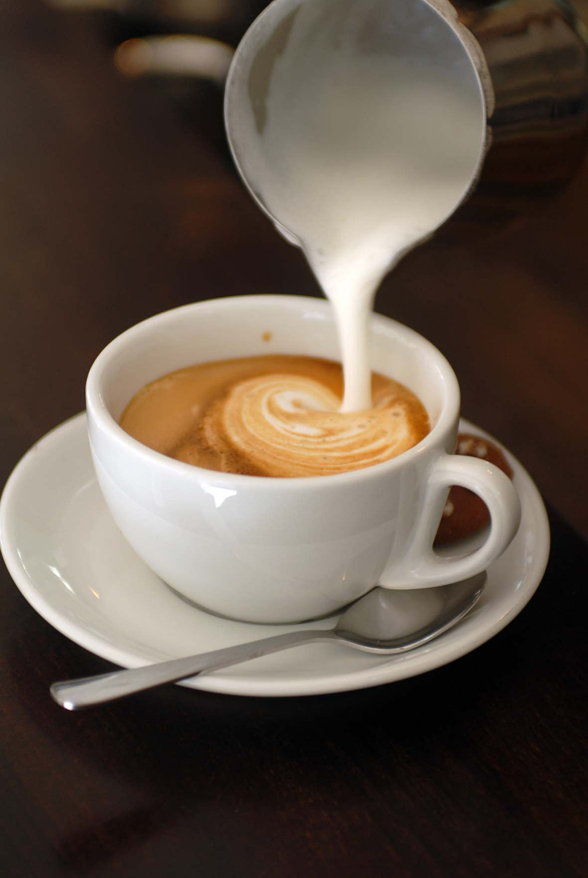 A cup of cappuccino on a saucer with milk being poured into it.