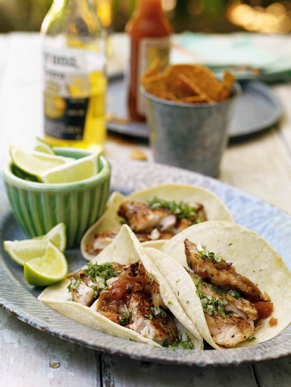 Enamel platter of three grilled red snapper tacos topped with cilantro and line, with lime wedges, beer, and chips on the side
