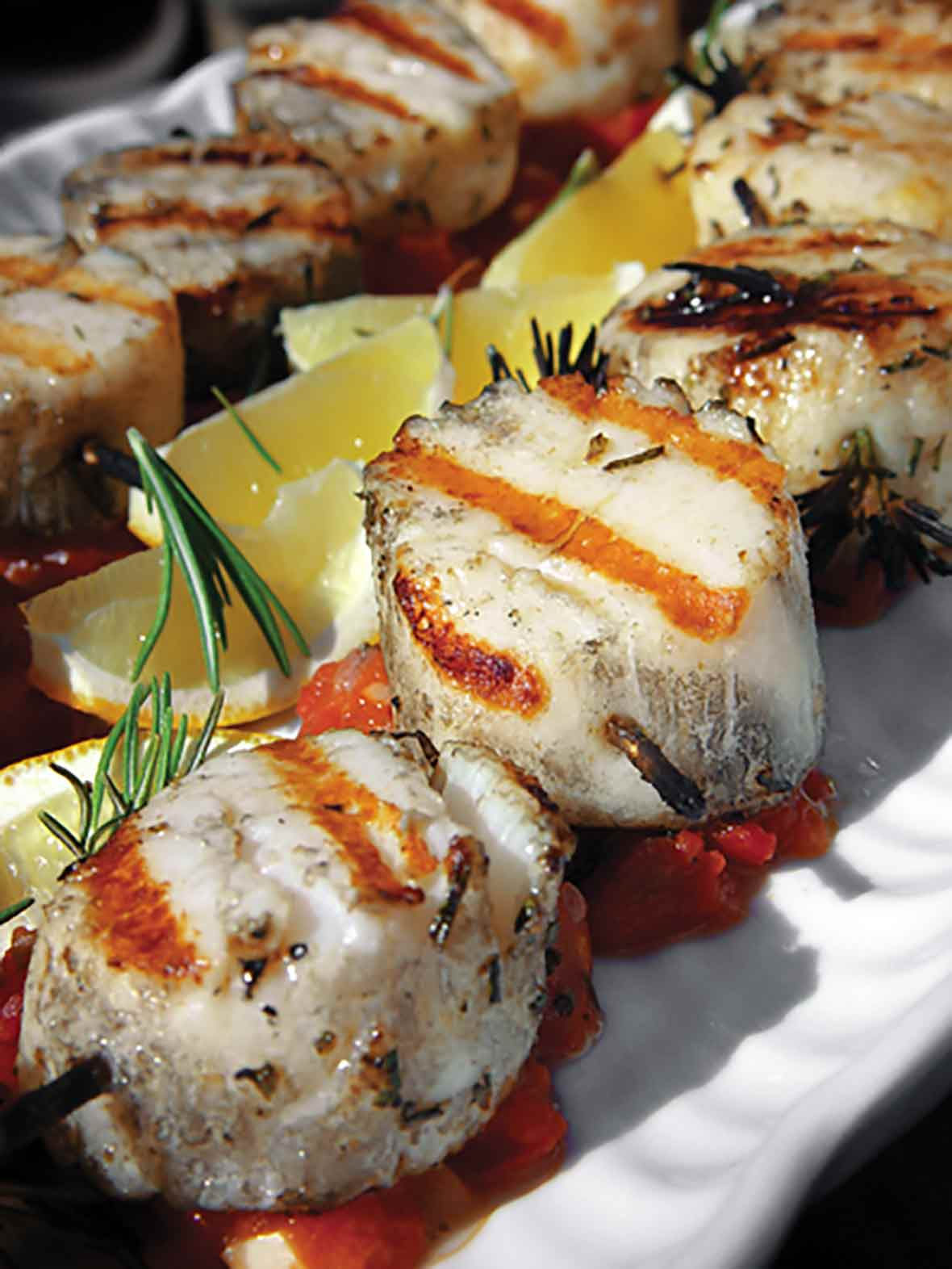 Grilled scallops are threaded on rosemary skewers and sitting on a bed of tomato chutney