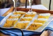 A platter of herb omelettes stuffed with ricotta on a wooden tray with two glasses of Champagne.