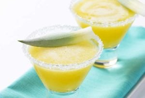 Two glasses filled with pineapple-tequila smoothie, rimmed with sugar, topped with line wedges on a napkin