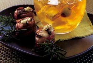 Prosciutto scallop pops on a plate with lemon artichoke pesto