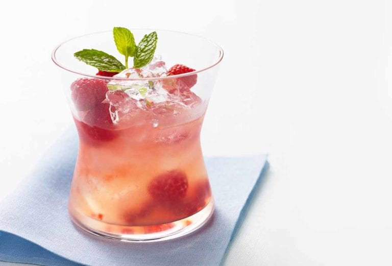 Glass filled with raspberry lemonade spiked with tequila, raspberries, mint, and ice