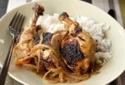 Plate of Senegalese grilled chicken legs and thighs cooked with onions and lemon, rice on the side