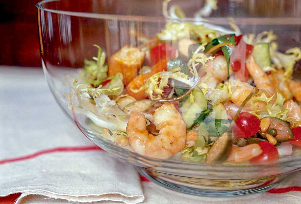 A glass bowl filled with cooked shrimp, grilled focaccia, cucumbers, tomatoes, capers, olives, and frisee