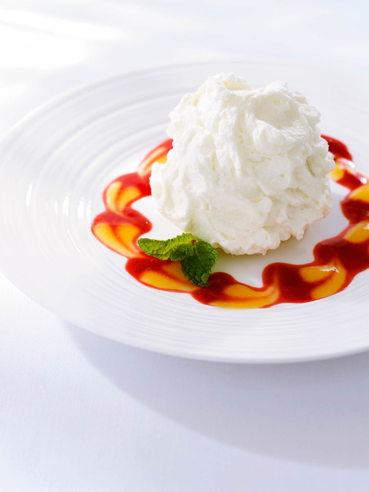 Plate of three milks cake, topped with whipped cream, with red and orange sauces