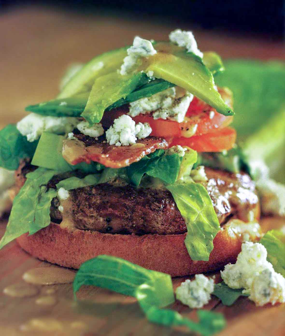 A turkey cobb burger--a turkey hamburger on a bun with lettuce, tomato, bacon, blue cheese, and avocado