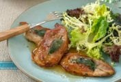 Blue plate with two veal scaloppine topped with prosciutto and sage, a salad