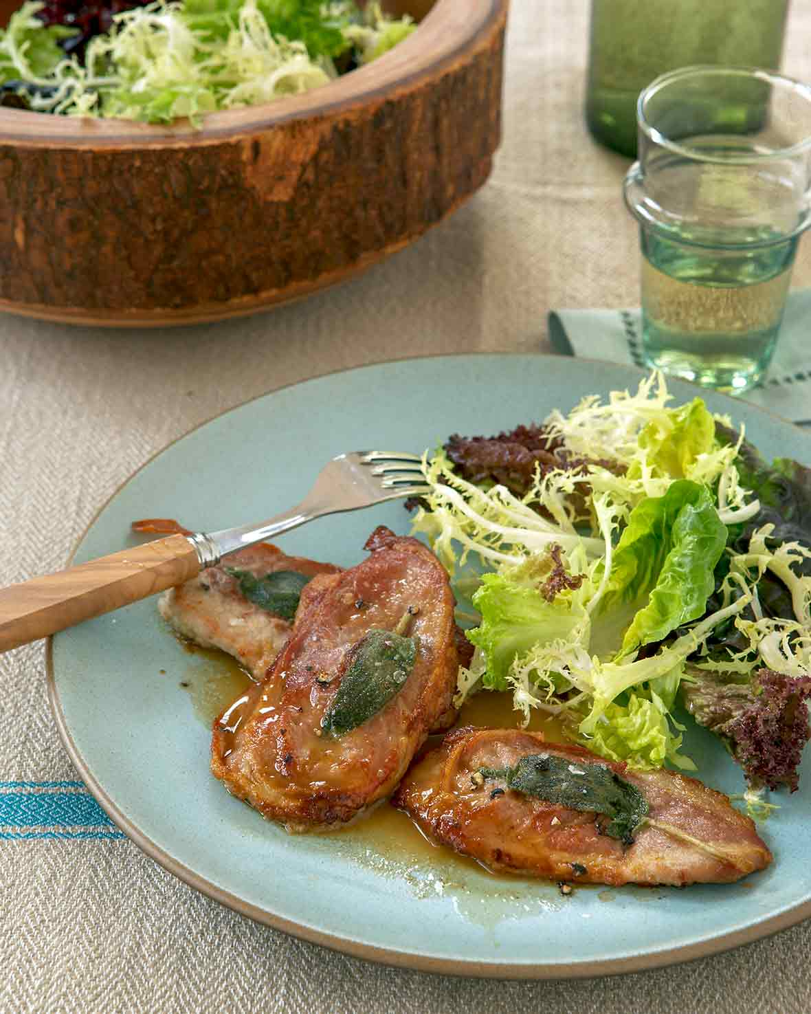 Blue plate with two veal scaloppine topped with prosciutto and sage, a salad, salad bowl, wine