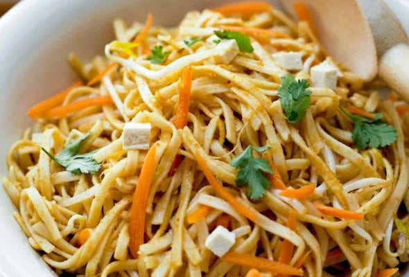 Close-up of a white bowl filled with asian noodle salad with peanut dressing, slivered carrots, tofu, and cilantro