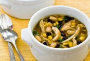 Two bowls of black and white chicken chili on a yellow placemat with two spoons beside the bowls.