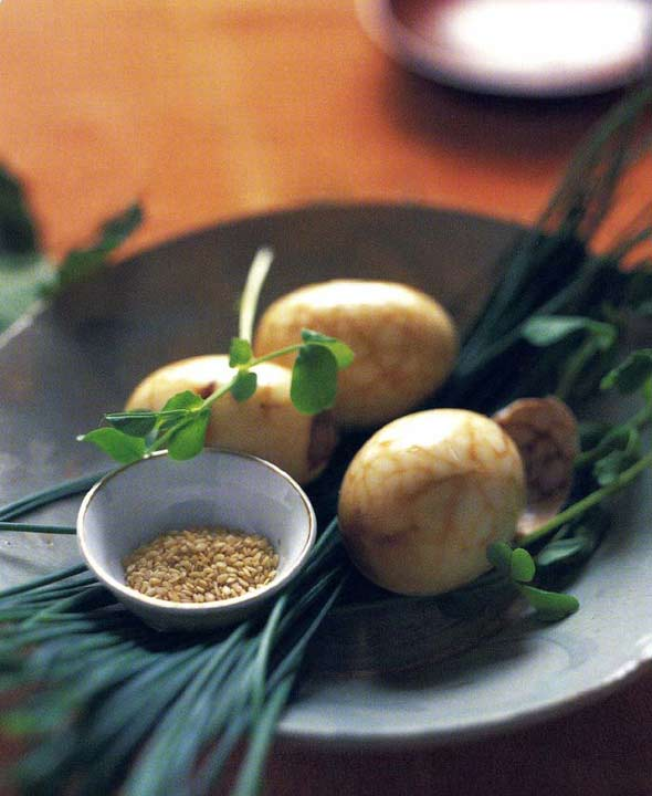 Three Chinese tea eggs in a black bowl with chives, pea shoots, and a small bowl of sesame seeds.