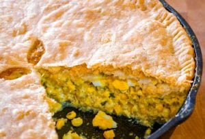 A corn pie, with a sliced remove, the filling of corn, egg, celery, onion, parsley can be seen