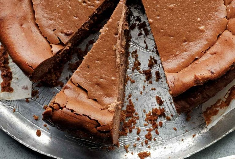 An espresso cheesecake on a silver platter with two slices cut from it.