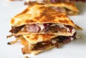 Two pieces of goat cheese quesadillas filled with radicchio, tapenade, and goat cheese stacked on top of each other.