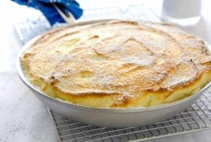 A skillet lemon souffle made entirely in a frying pan, sitting on a wire rack, blue cloth wrapped around the handle