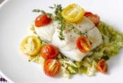 An oven-roasted halibut fillet with cherry tomatoes, and thyme on a bed of savoy cabbage