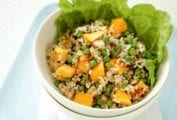 Salad of papaya, green peas, rice with a leaf of lettuce in a bowl in a tray