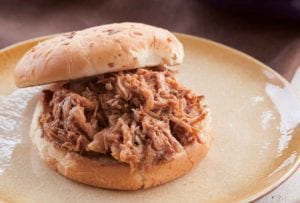 Slow cooker pulled pork piled on a bun on a plate.
