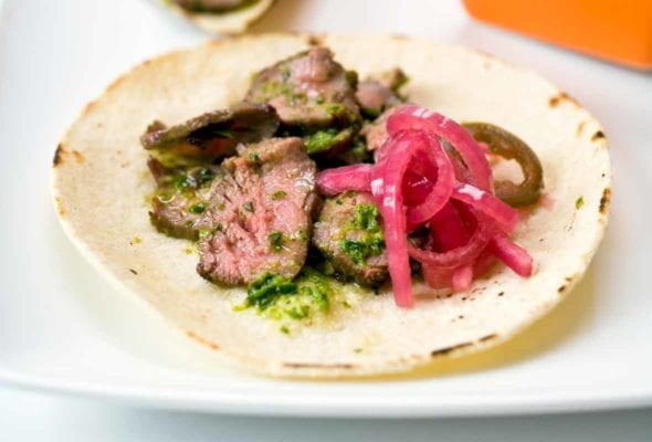 Steak tacos made of soft flour tortilla, slice steak, salsa verde, pickled onions