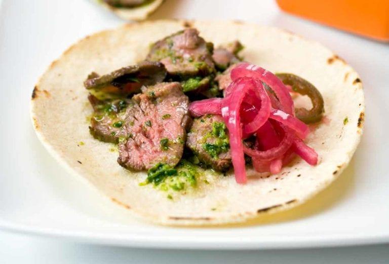 Steak tacos made of soft flour tortilla, slice steak, salsa verde, pickled onions