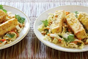 Two plates of warm cabbage salad with fried crispy tofu, carrots, cilantro on woven placemats