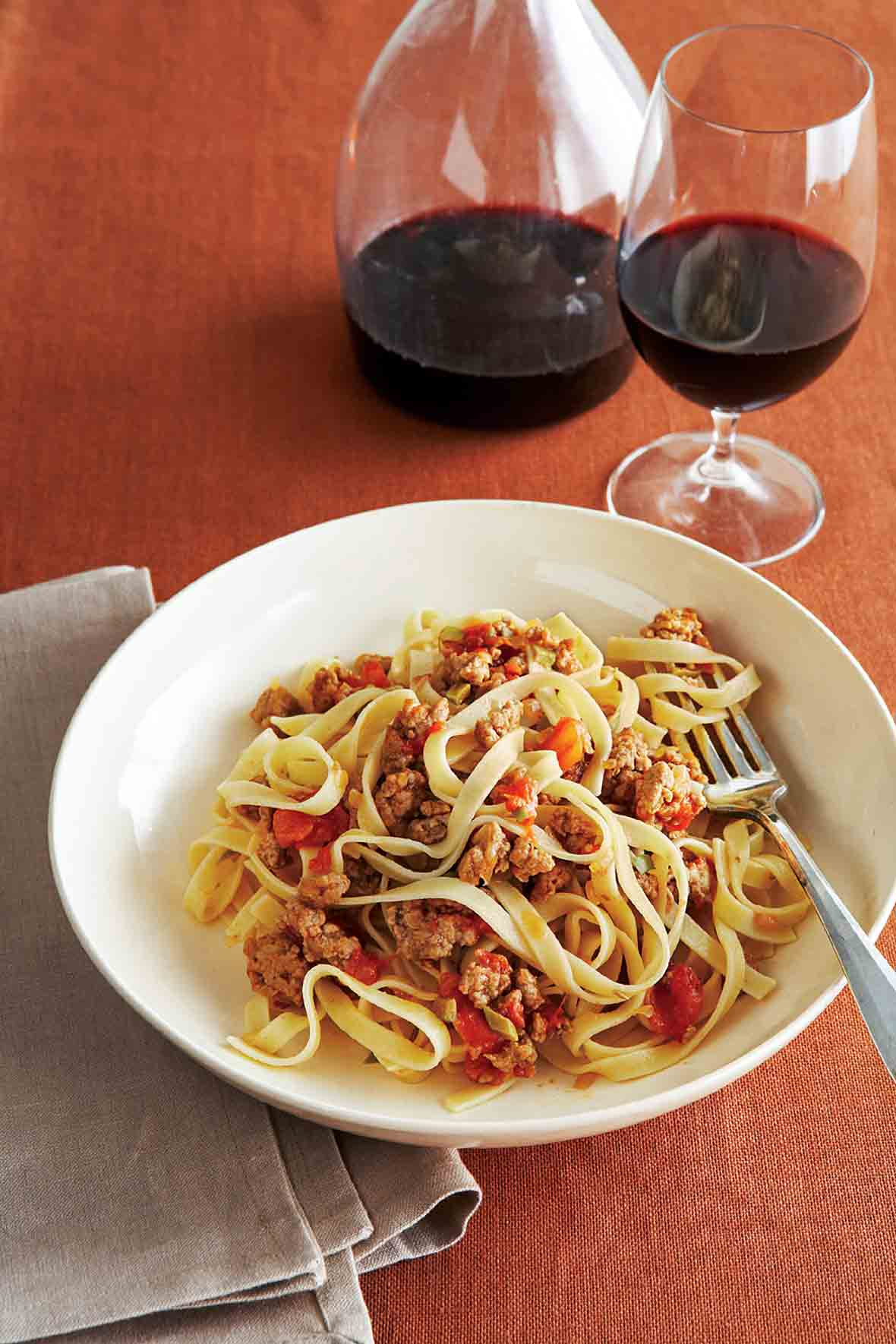 A wide white bowl filled with fettuccine with a savory veal sauce and a carafe and glass of wine in the background.