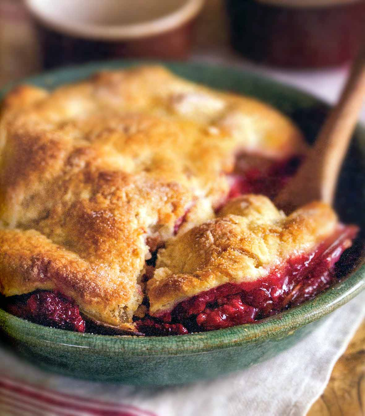 A pear and raspberry pandowdy or cobbler in a green bowl with a pastry top, wooden spoon inside