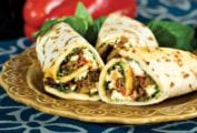 Three Mediterranean eggplant wraps--cooked eggplant, goat cheese, peppers, onions, and basil rolled in a flatbread on a plate