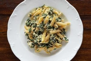 A white serving bowl filled with penne with spinach-ricotta sauce.