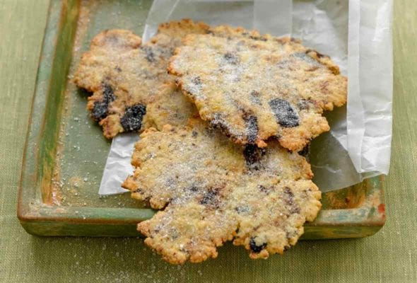 Irregular wafer cookies dotted with lemon and black olives in a wax paper wrapper on a green wood tray