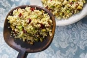 A large wooden spoon with a scoop of quinoa salad with pistachios and cranberries being held over a white bowl filled with the salad.