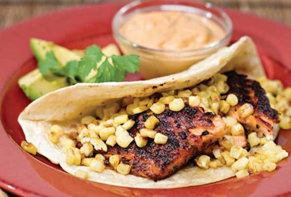 A wild salmon taco with roasted corn and chile adobo cream on the side on a red plate.