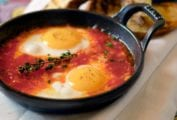 Two eggs in a tomato sauce, topped with a sprig of thyme in a cast iron skillet
