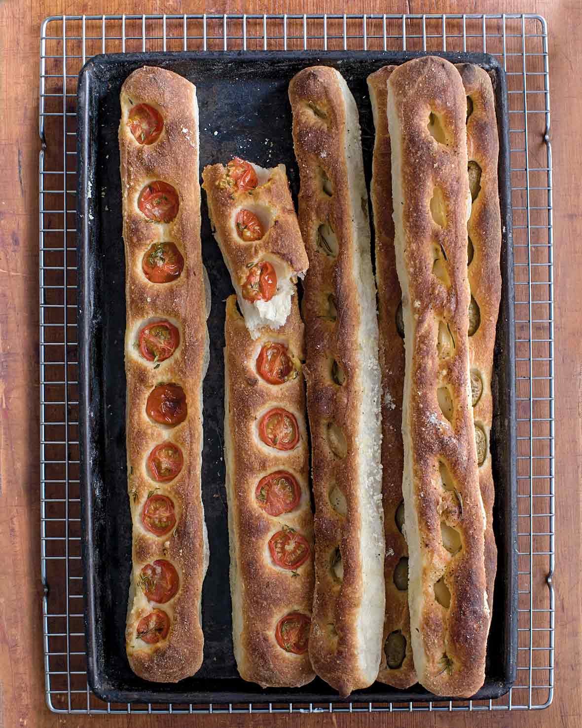 Five no-knead baguettes by Jim Lahey, some with sliced tomato, some with garlic and olives