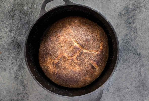 Cast-iron pot with a loaf of Jim Lahey's no-knead whole-wheat bread on a gray background