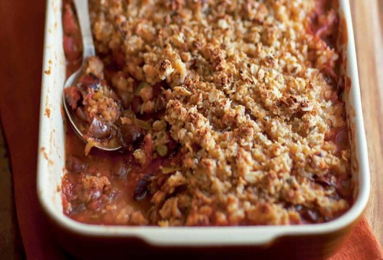 A rectangular casserole dish filled with spicy tomato crumble, and a spoon resting in it.