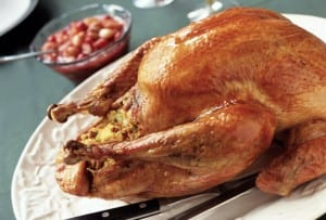 A cooked turkey filled with bread stuffing with bacon, apples, sage, and caramelized onions on a white platter.