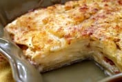 A deep baking dish containing celery root and potato gratin with one piece missing