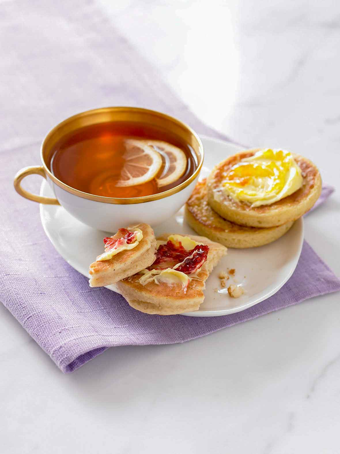 Two English crumpets, one with butter and jam, one with butter and marmalade, on a plate, with a cup of tea nearby