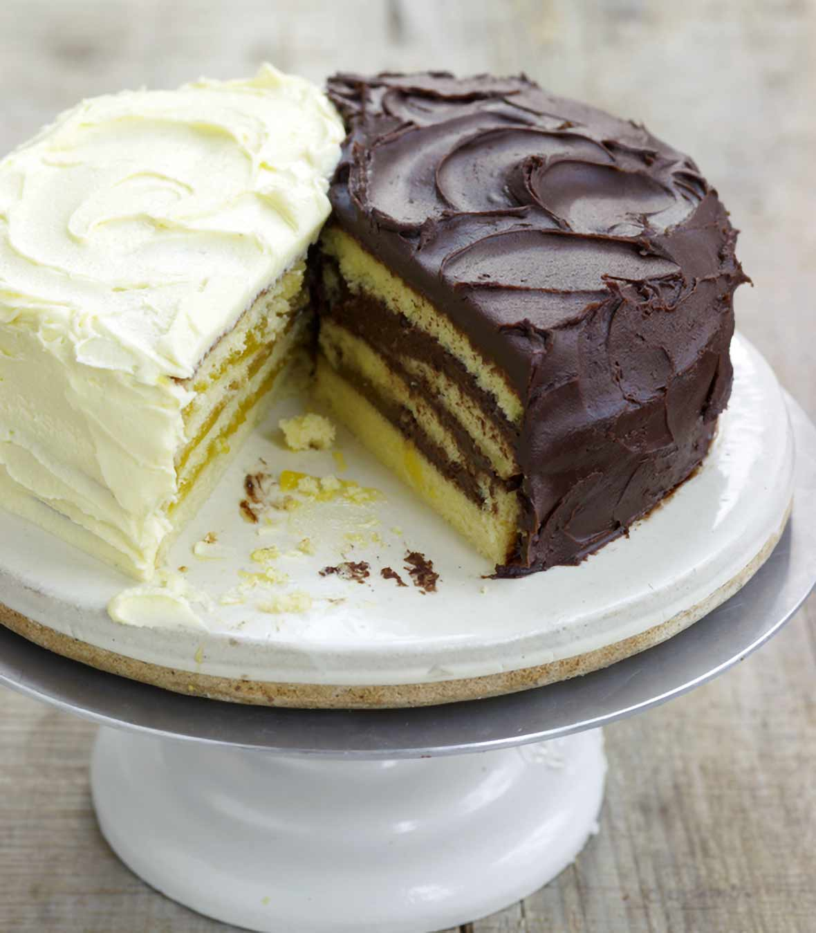 Cake stand with a half of a lemon Doberge layer cake and a half of a chocolate Doberge layer cake