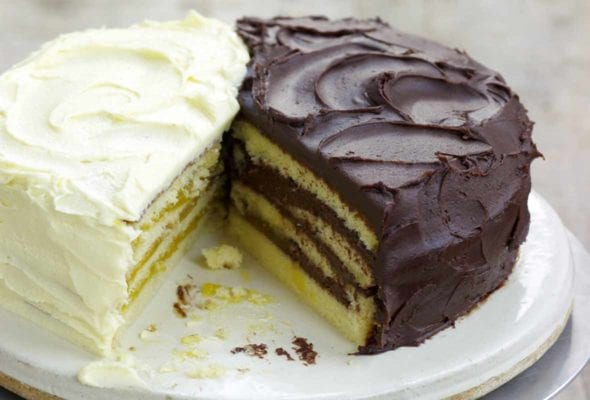 Cake stand with a half of a lemon Doberge layer cake and a half of a chocolate Doberge layer cake