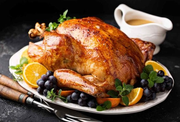 An old-fashioned roast turkey on a platter with bunches of grapes and orange slices and a boat of gravy behind it.