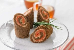 A white cake stand with four spirals of pumpernickel bread, salmon mousse, and smoked salmon