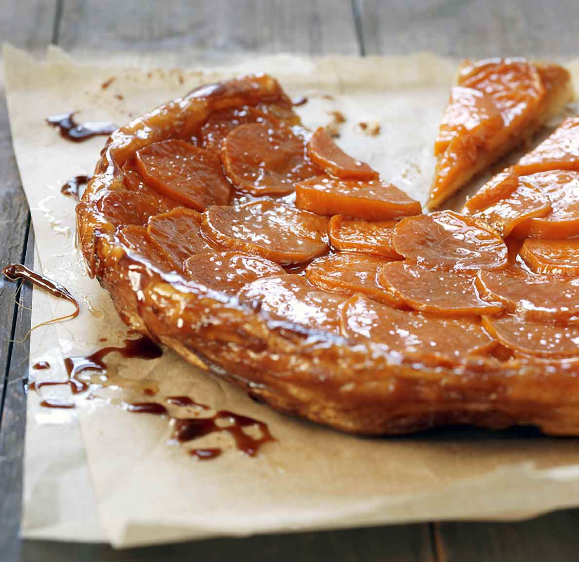 A tart tatin on parchment made with puff pastry crust and on top slices of caramelized sweet potatoes
