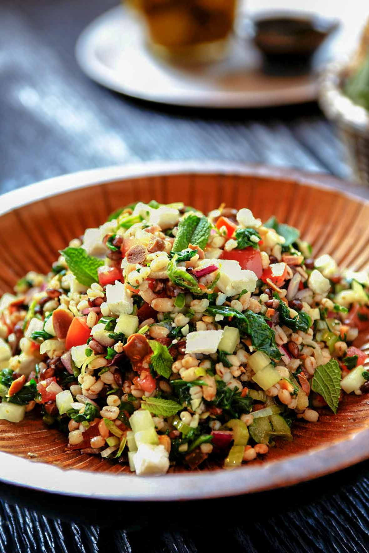 A wooden bowl of barley salad with shopped spinach, tomatoes, feta cheese, onion, and olives